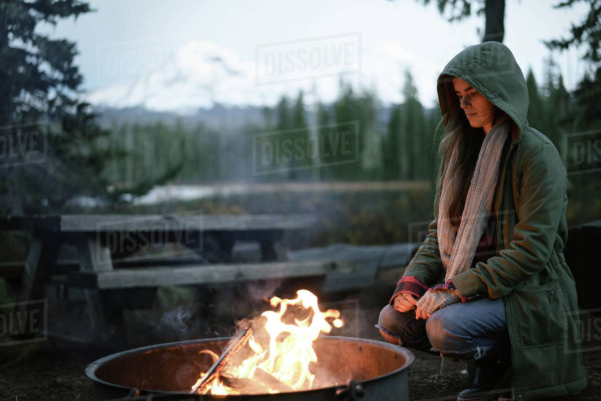 Woman crouched by campfire with hood up Royalty-free stock photo