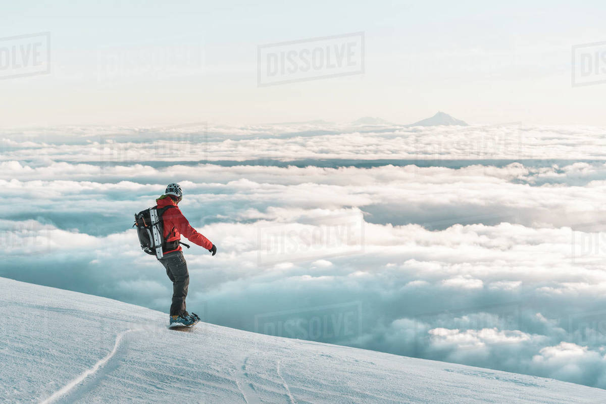 Snowboarder riding down mountain at sunset above clouds Royalty-free stock photo