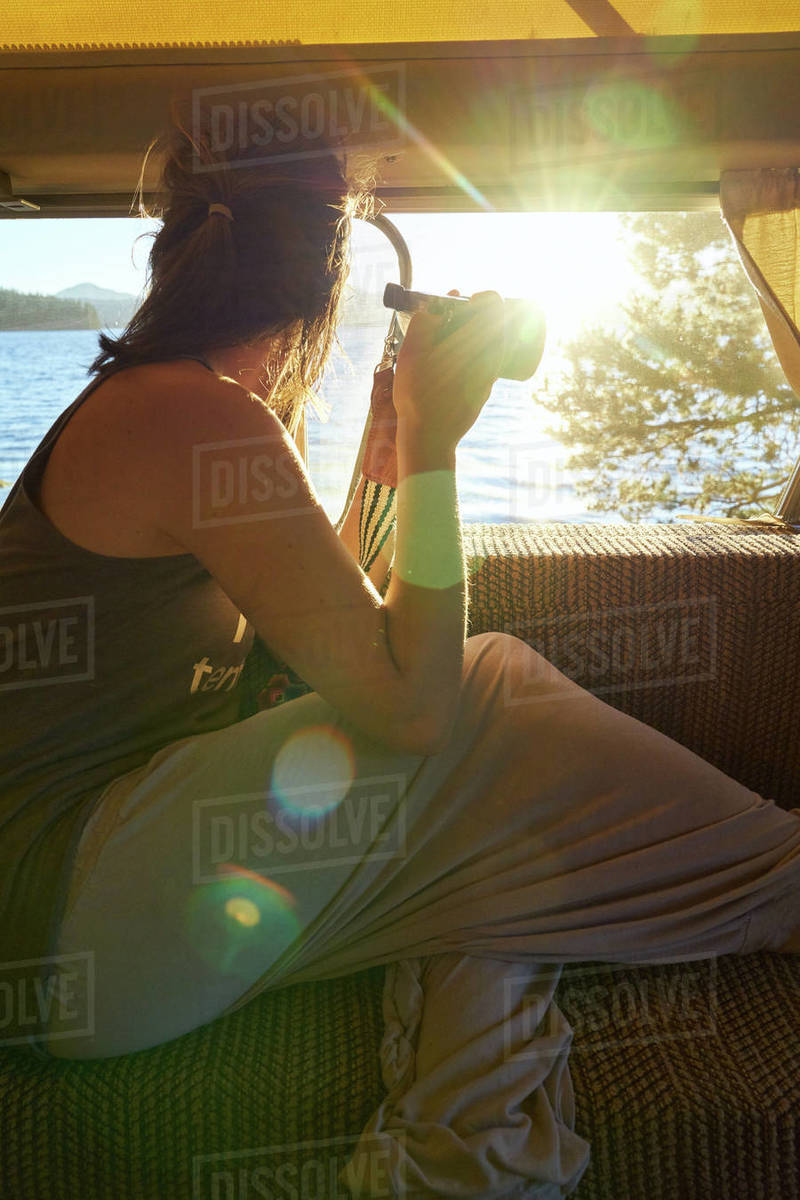 Young woman sitting in camper holding a camera looking out at a lake Royalty-free stock photo