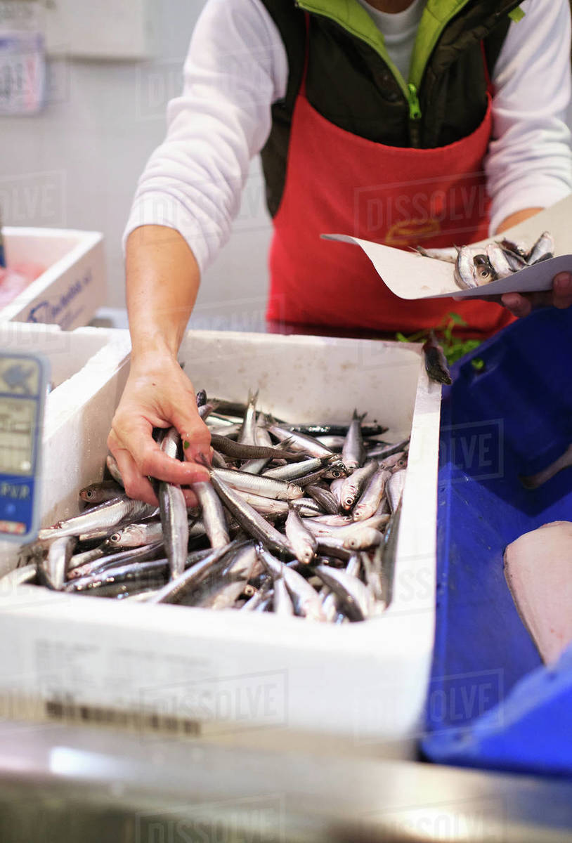 Young woman works in a fish shop, prepares blue fish to sell to her cu Royalty-free stock photo
