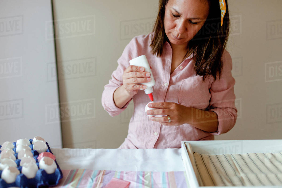 Woman making a craft projects with white glue, confetti, eggs Royalty-free stock photo