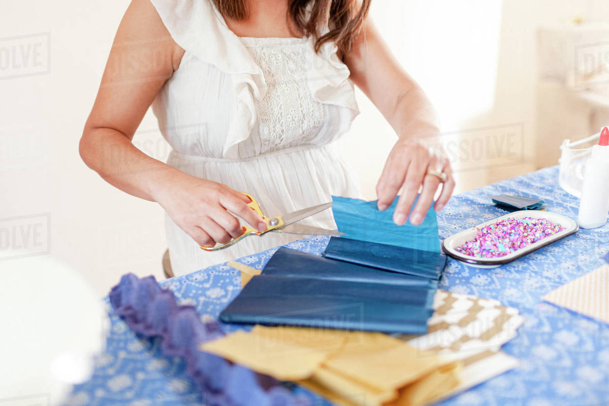 Closeup woman by art table cutting gold tissue paper with scissors Royalty-free stock photo