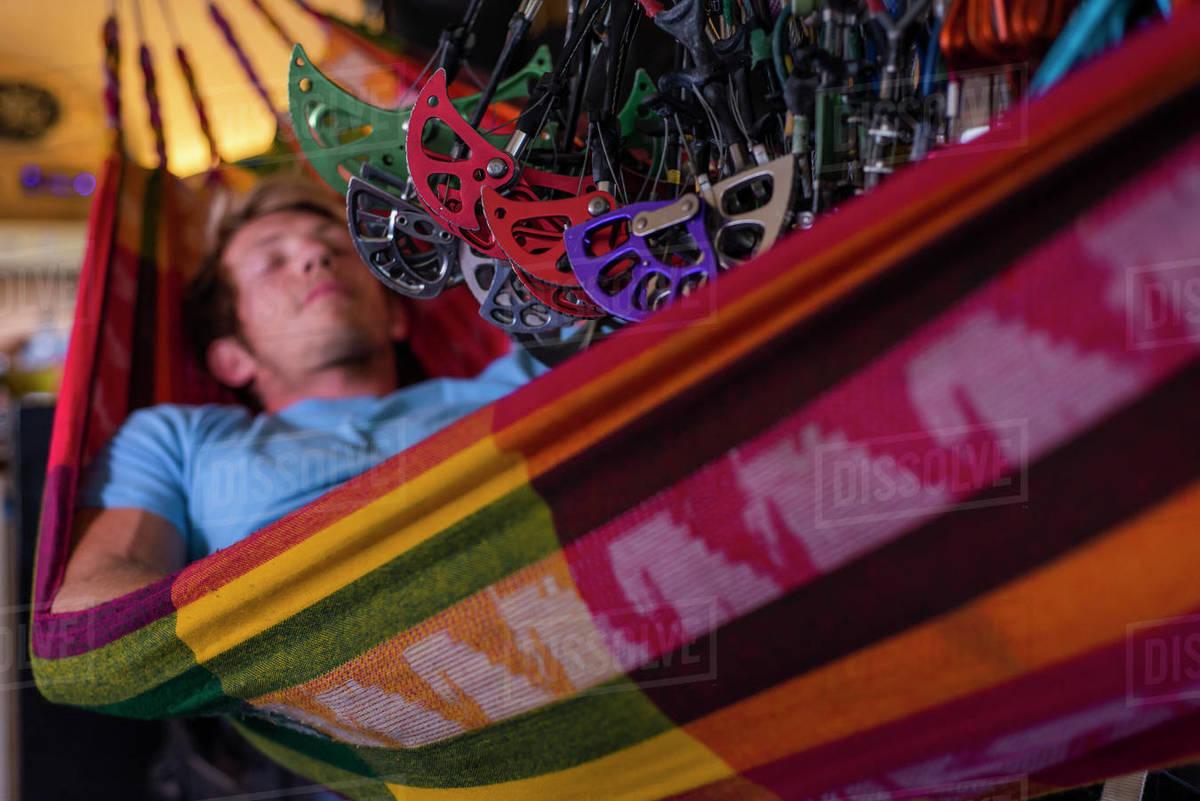 Man sleeping in hammock inside bus under lots of climbing gear hanging Royalty-free stock photo