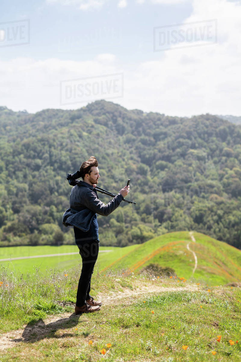 Young man takes photo with phone while holding camera over shoulder Royalty-free stock photo