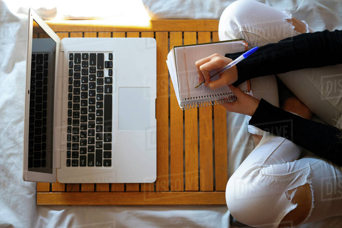 Top view of a woman working in bed and writing on her datebook. Royalty-free stock photo