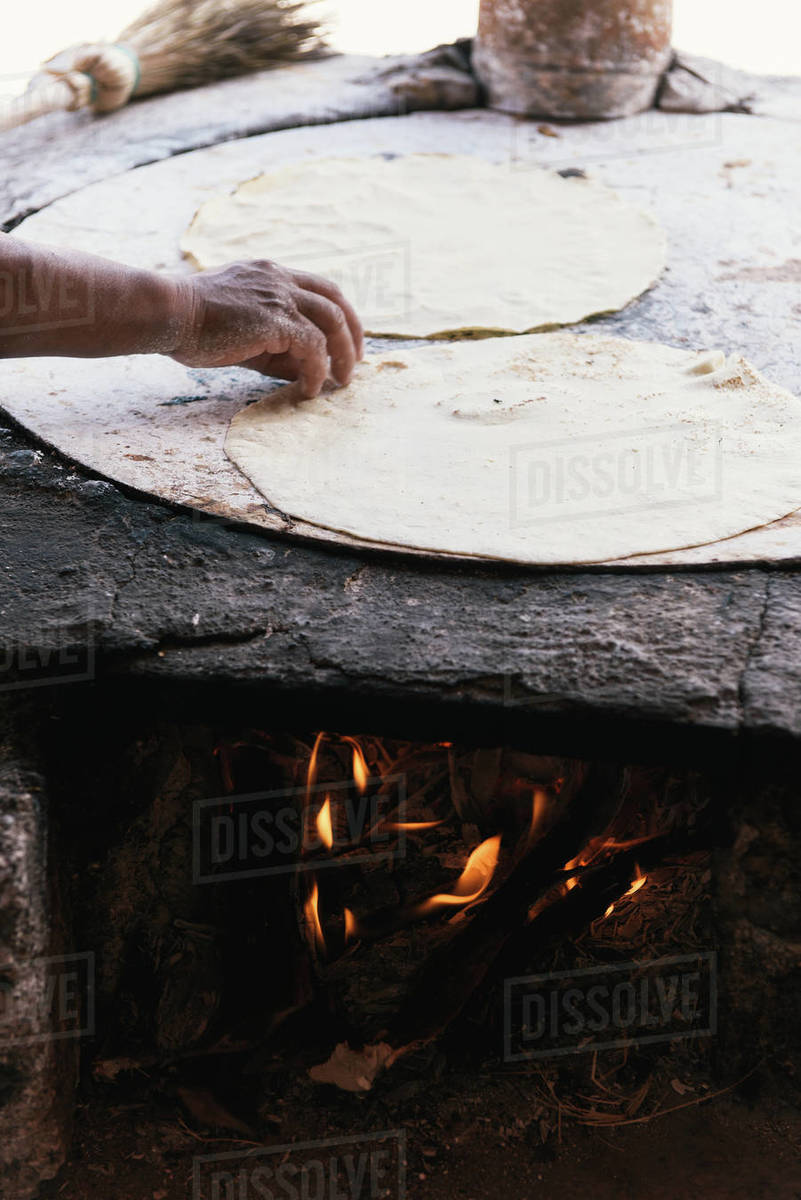 Side view of fresh tortilla cooking on an open fire comal Royalty-free stock photo