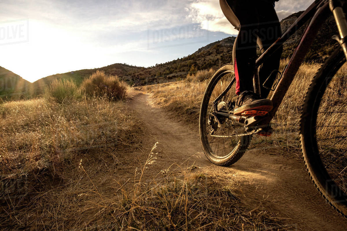 Young woman mountain biking during sunset in mountains Royalty-free stock photo