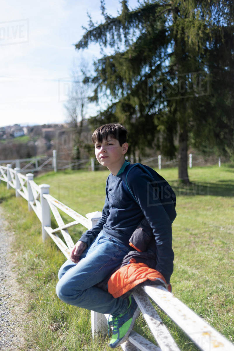 Young teenager male sitting on countryside fence looking camera Royalty-free stock photo