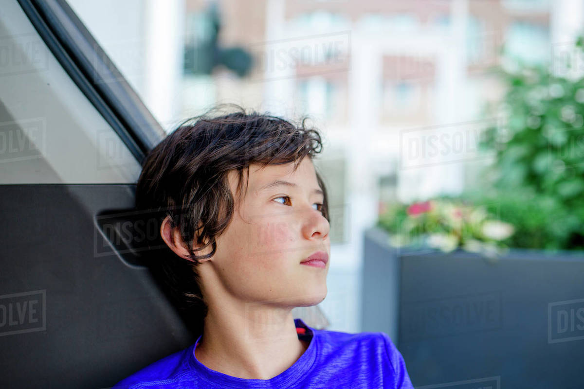 A boy traveling on public transportation gazes out the window Royalty-free stock photo