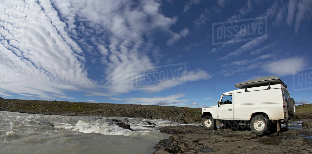 White SUV standing at the edge of a waterfall Royalty-free stock photo