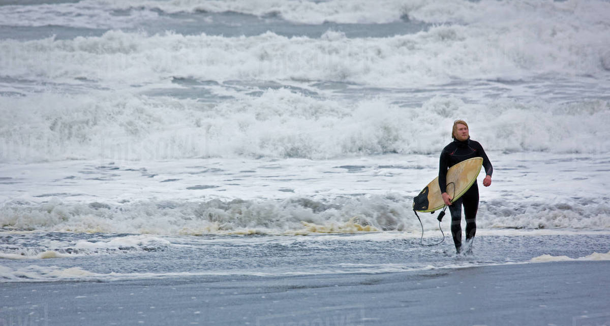 Young man walks with surfboard out of the water in Iceland Royalty-free stock photo