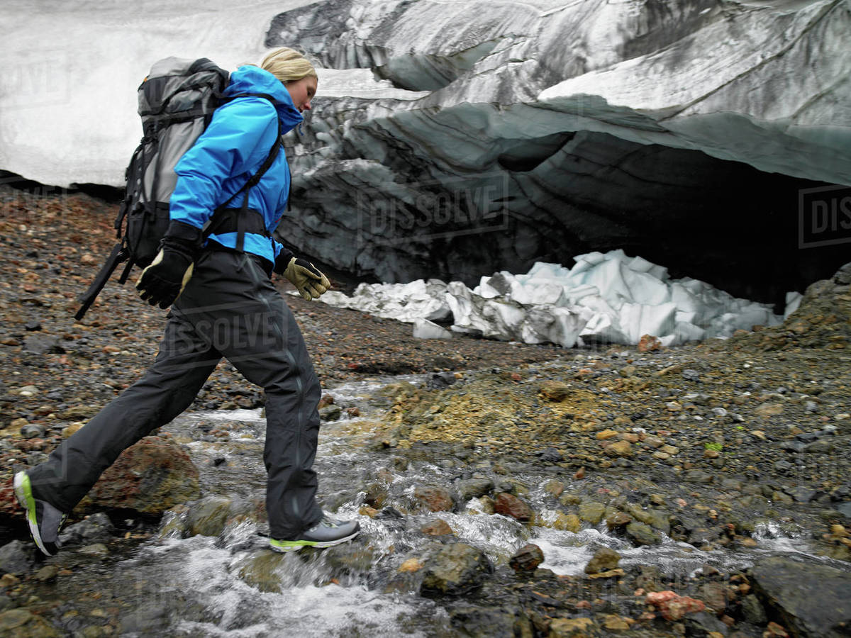 Young woman crossing river at Hrafntinnusker in Iceland Royalty-free stock photo