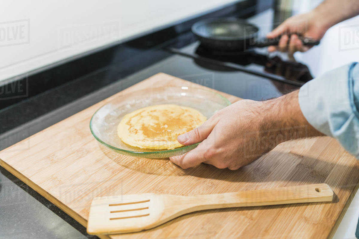 Man cooking in the kitchen in a denim shirt. An anonymous man is holding a pan with a pancake on a plate Royalty-free stock photo