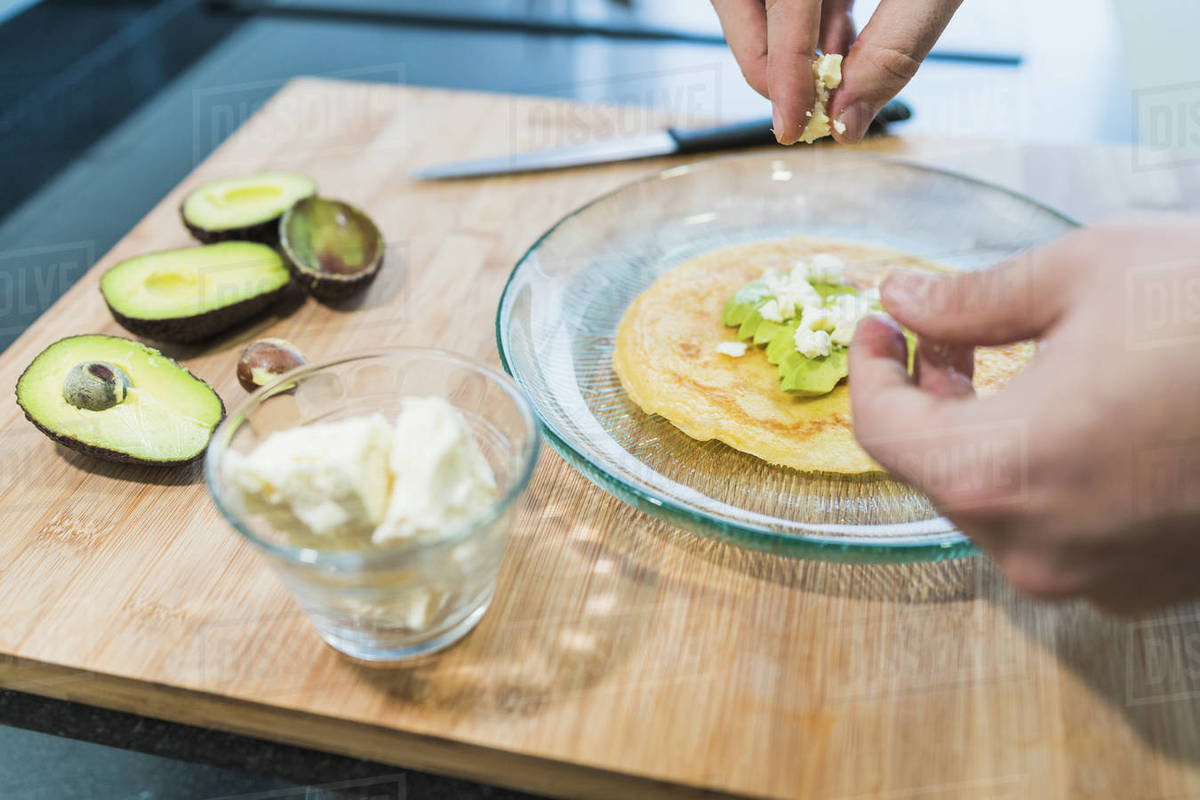 Man cooking in the kitchen in a denim shirt. An anonymous man is cooking pancakes with feta cheese and avocado Royalty-free stock photo