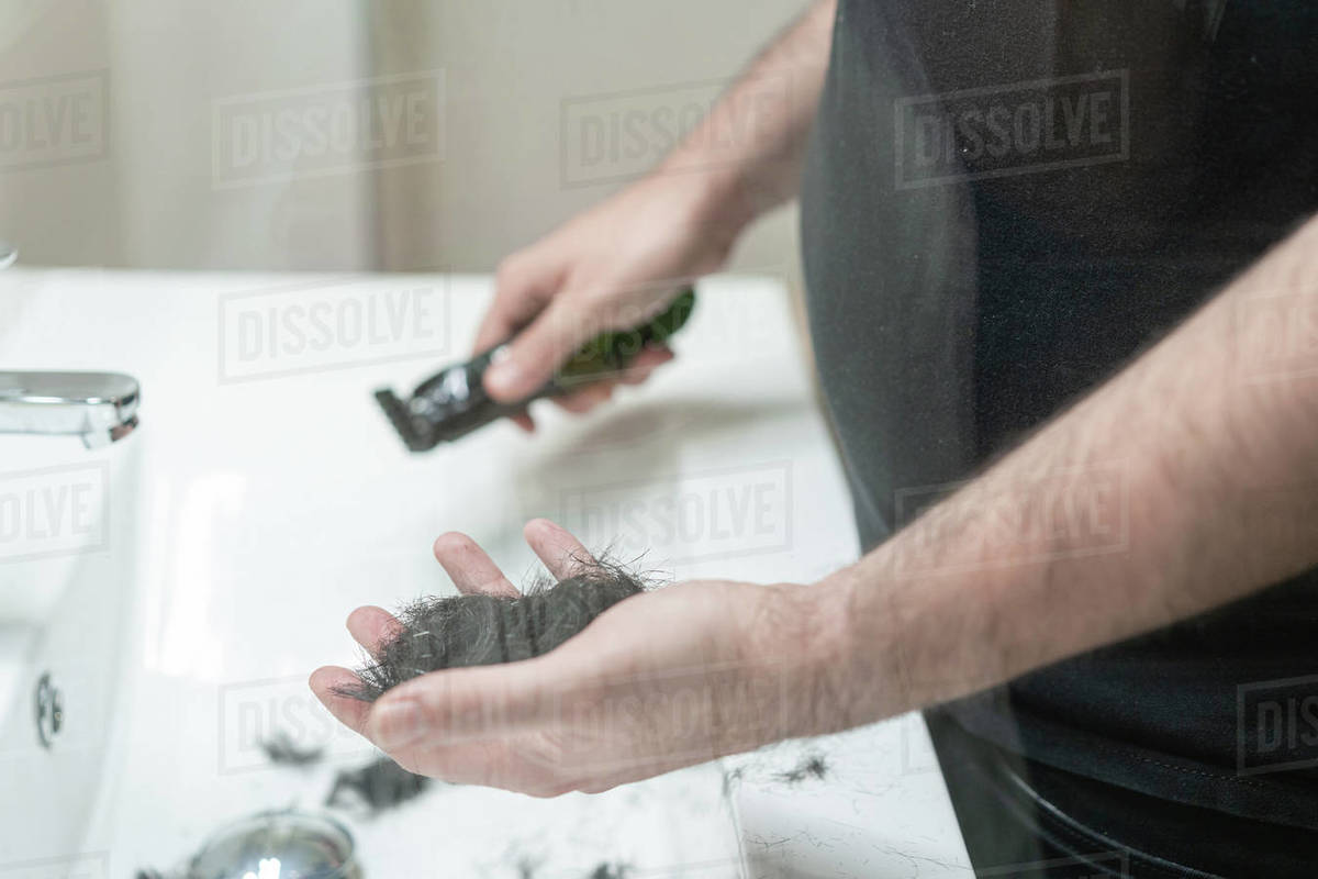 Self haircut. An anonymous man holds strands of hair in the bathroom with his hand Royalty-free stock photo