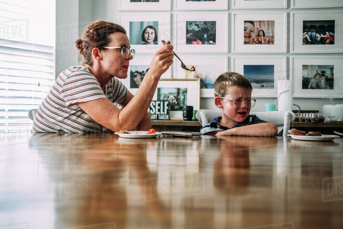 Mom offering bite of cake to crying son at the kitchen table Royalty-free stock photo