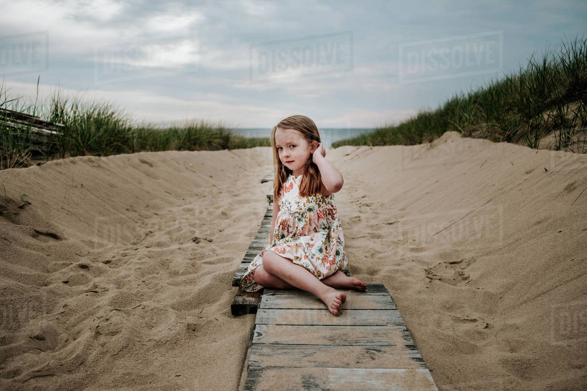 Young girl sitting on private board walk going out to lake Royalty-free stock photo