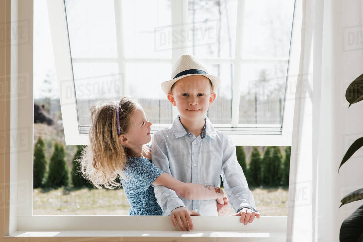 Brother and sister hugging whilst at home looking through a window Royalty-free stock photo
