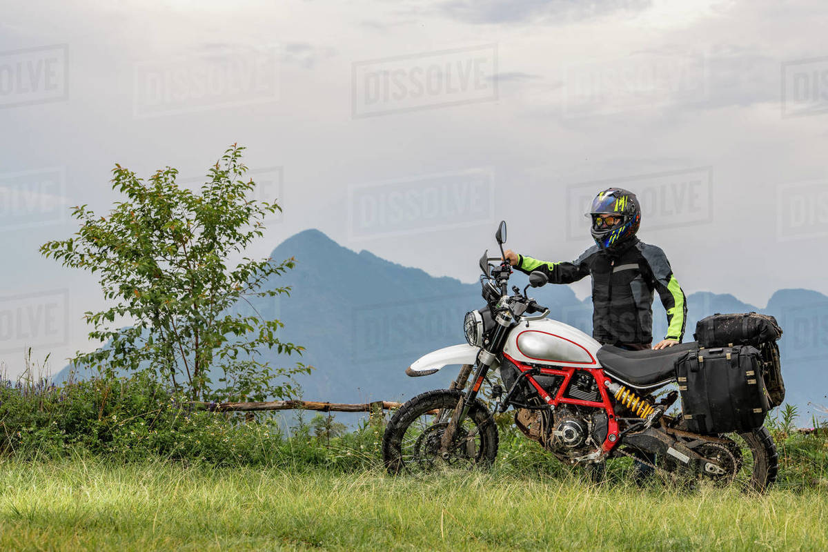 Man standing next to his scrambler type motorcycle Royalty-free stock photo