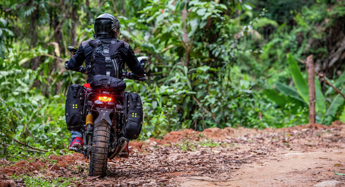 Woman riding her scrambler type motorcycle through forrest Royalty-free stock photo