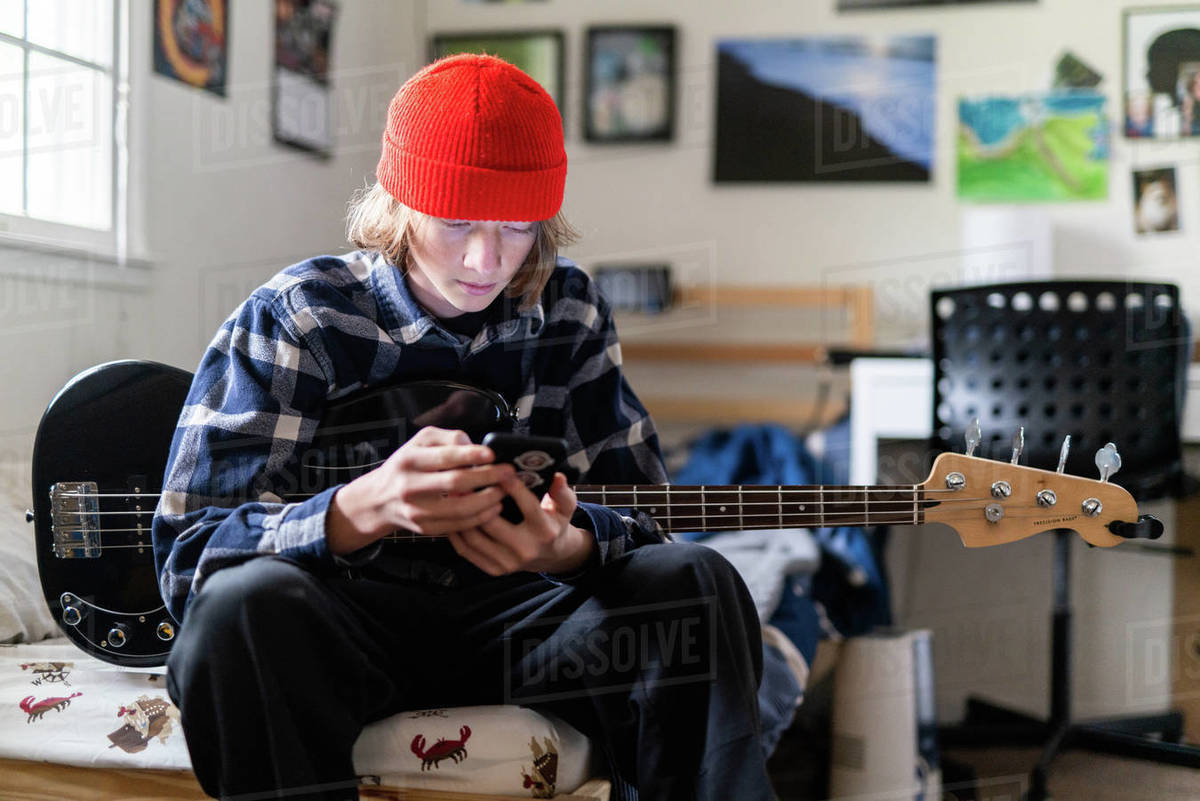 Teenager looking at smart phone while holding bass guitar in bedroom Royalty-free stock photo