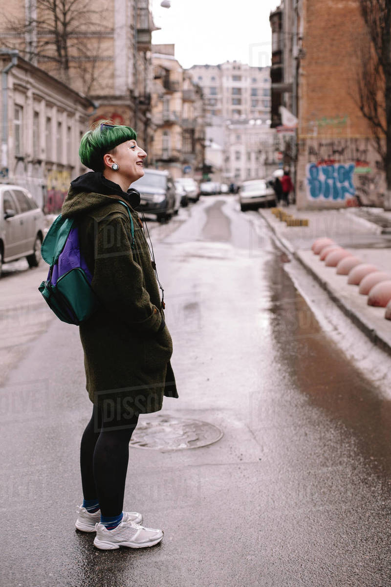 Happy non-binary female hipster standing on the road in city Royalty-free stock photo