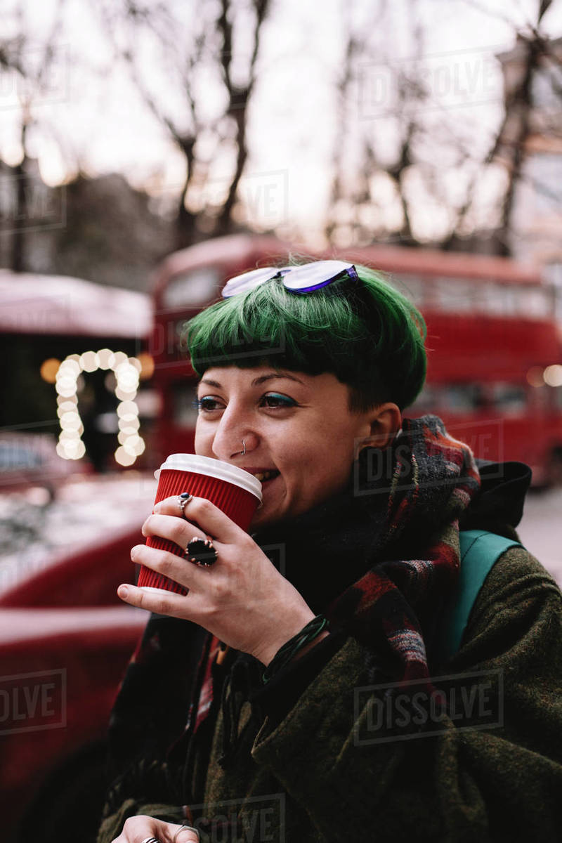 Happy non-binary hipster drinking coffee while walking on city street Royalty-free stock photo