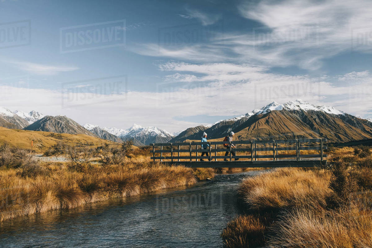 Couple of young hikers crossing a creek, Lake Clearwater, New Zealand Royalty-free stock photo