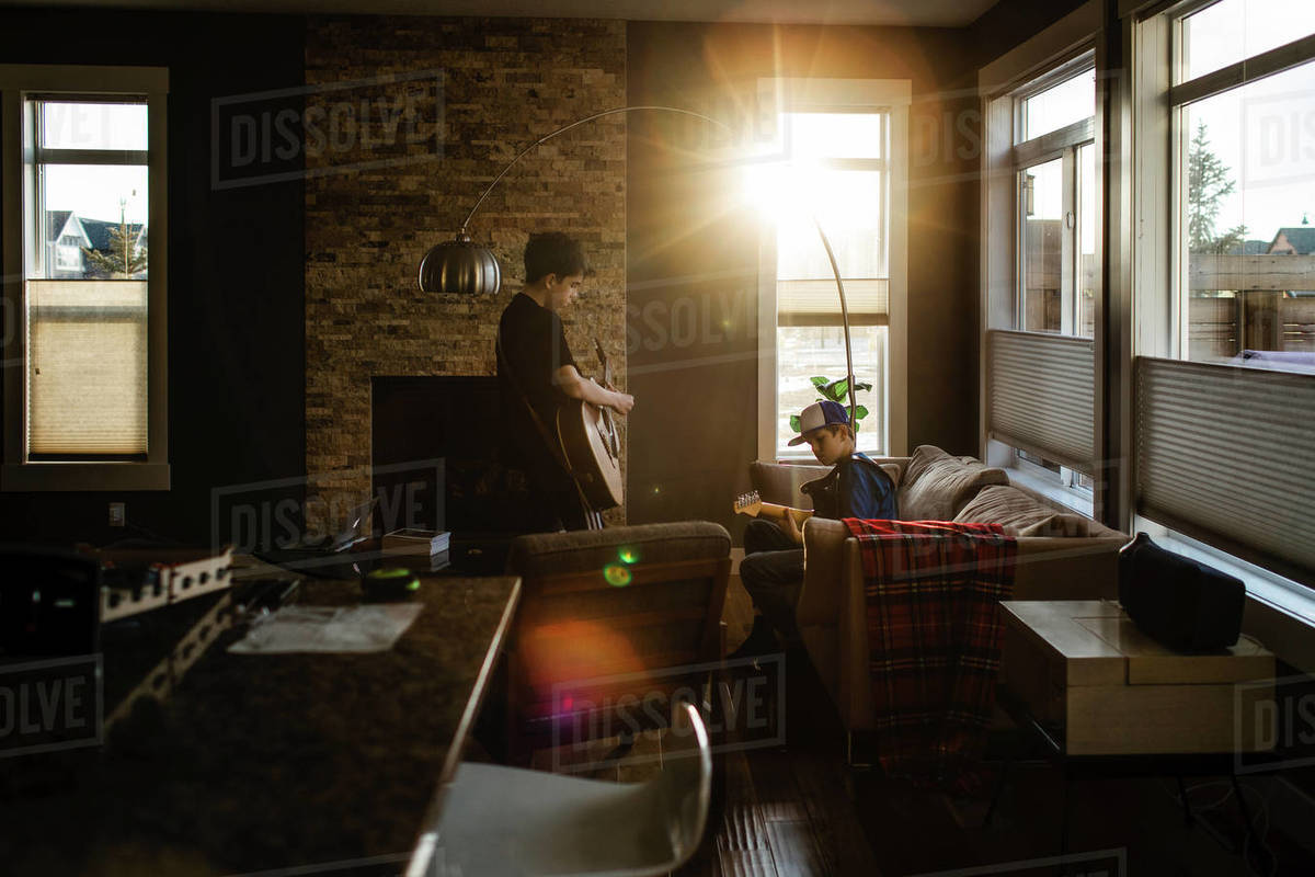 Brothers playing guitar at home with sun coming in window Royalty-free stock photo