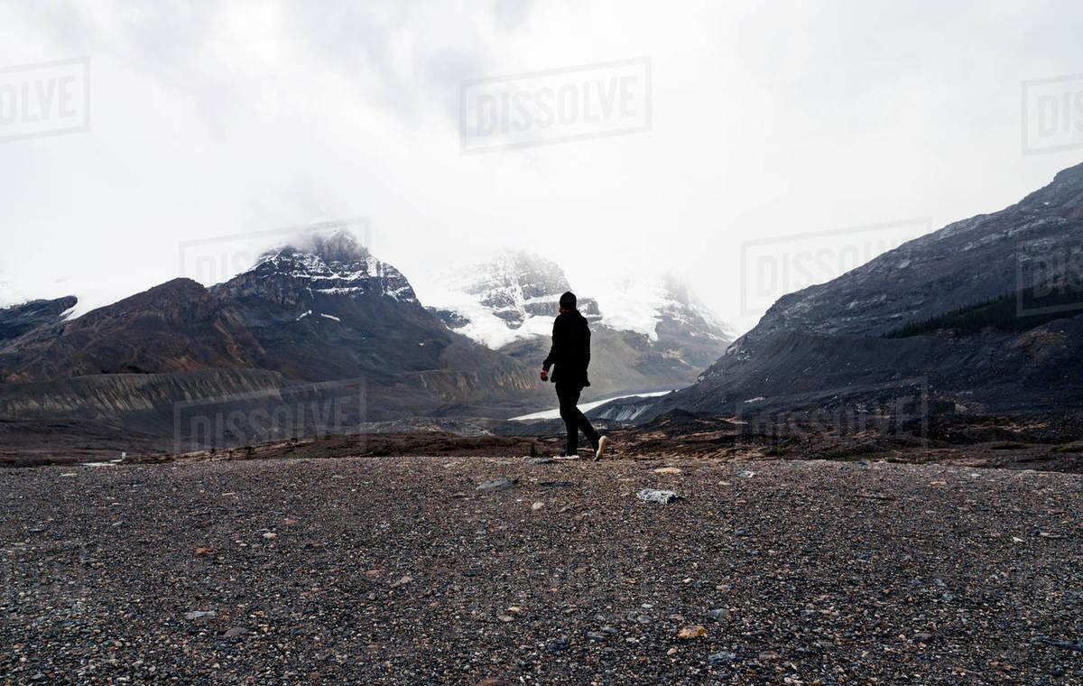 Lone Man Walks In Dramatic Mountain Peaks Royalty-free stock photo