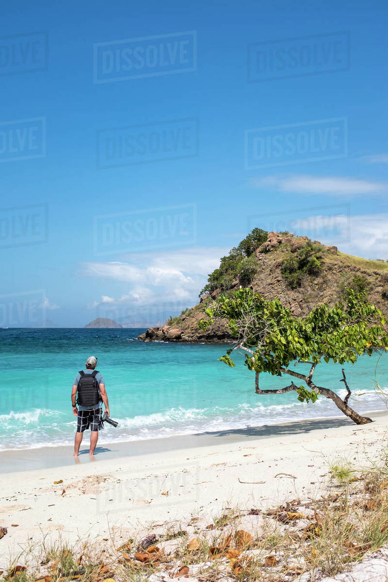 A photographer on Pink Beach in Komodo National Park, Indonesia. Royalty-free stock photo