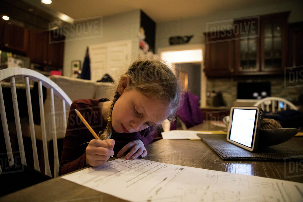 Close-in View of Young Girl At Kitchen Table Doing School Work Royalty-free stock photo
