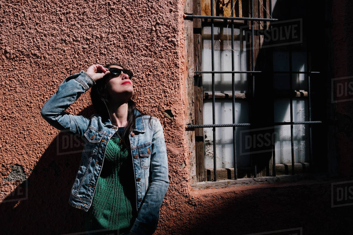 Young woman with black hair wearing sunglasses near a ruined house out Royalty-free stock photo