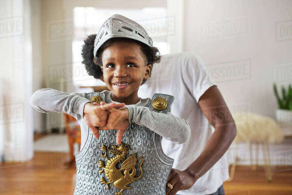 Father assisting cheerful boy in getting dressed as armor at home Royalty-free stock photo