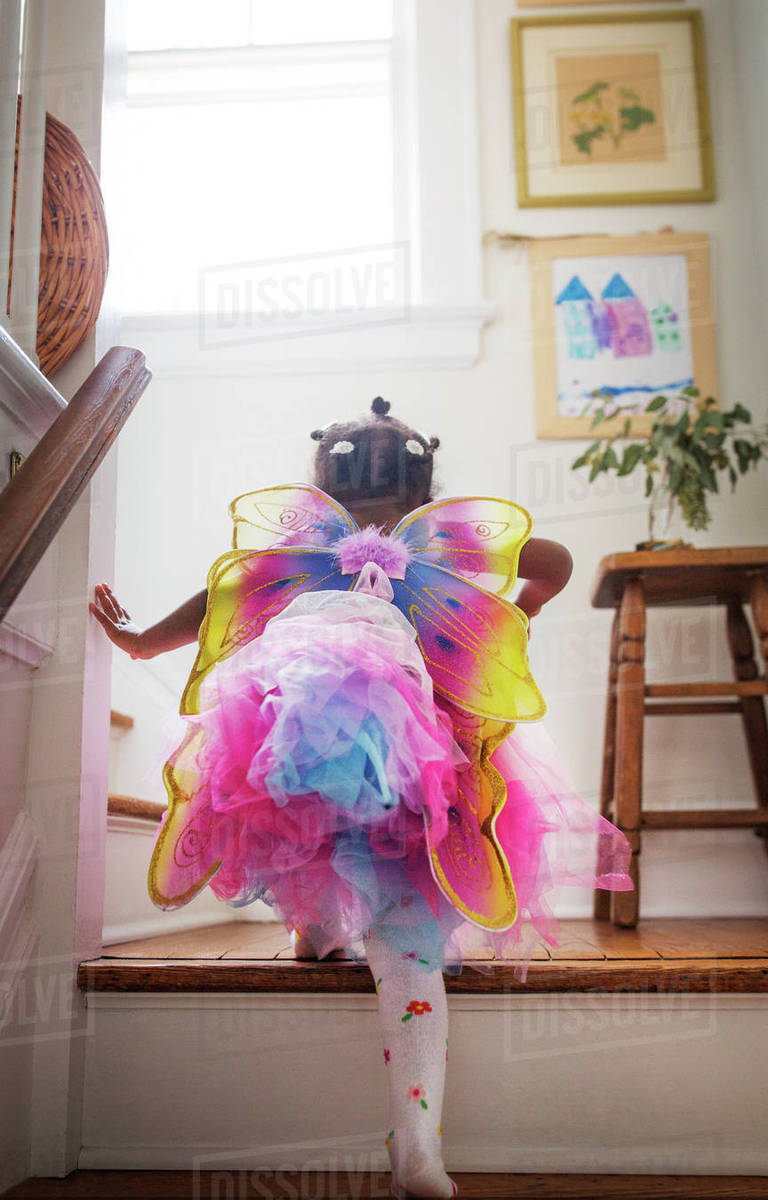 Rear view of girl in fairy costume moving up steps at home Royalty-free stock photo