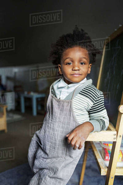 Portrait of confident boy leaning on blackboard at home Royalty-free stock photo
