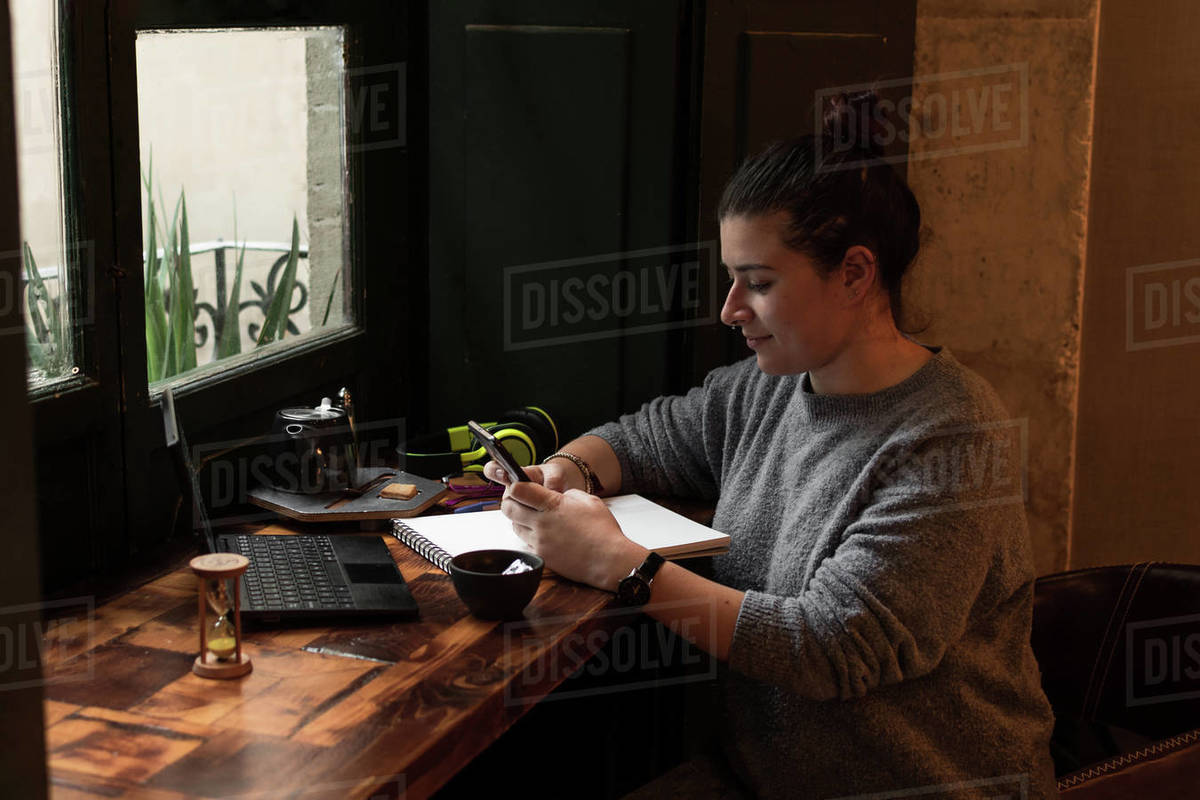 Young woman looks at her phone while studying in a retro pub Royalty-free stock photo