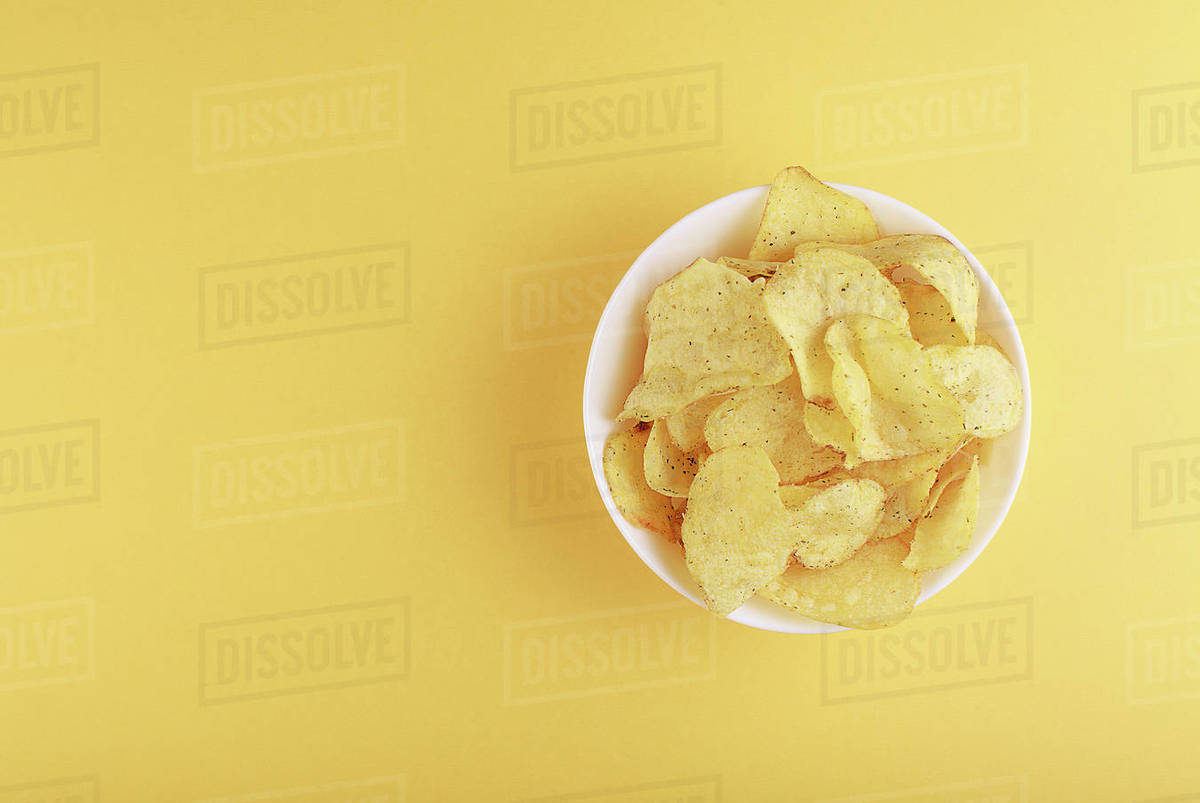 Crispy potato chips in bowl on yellow background, top view Royalty-free stock photo