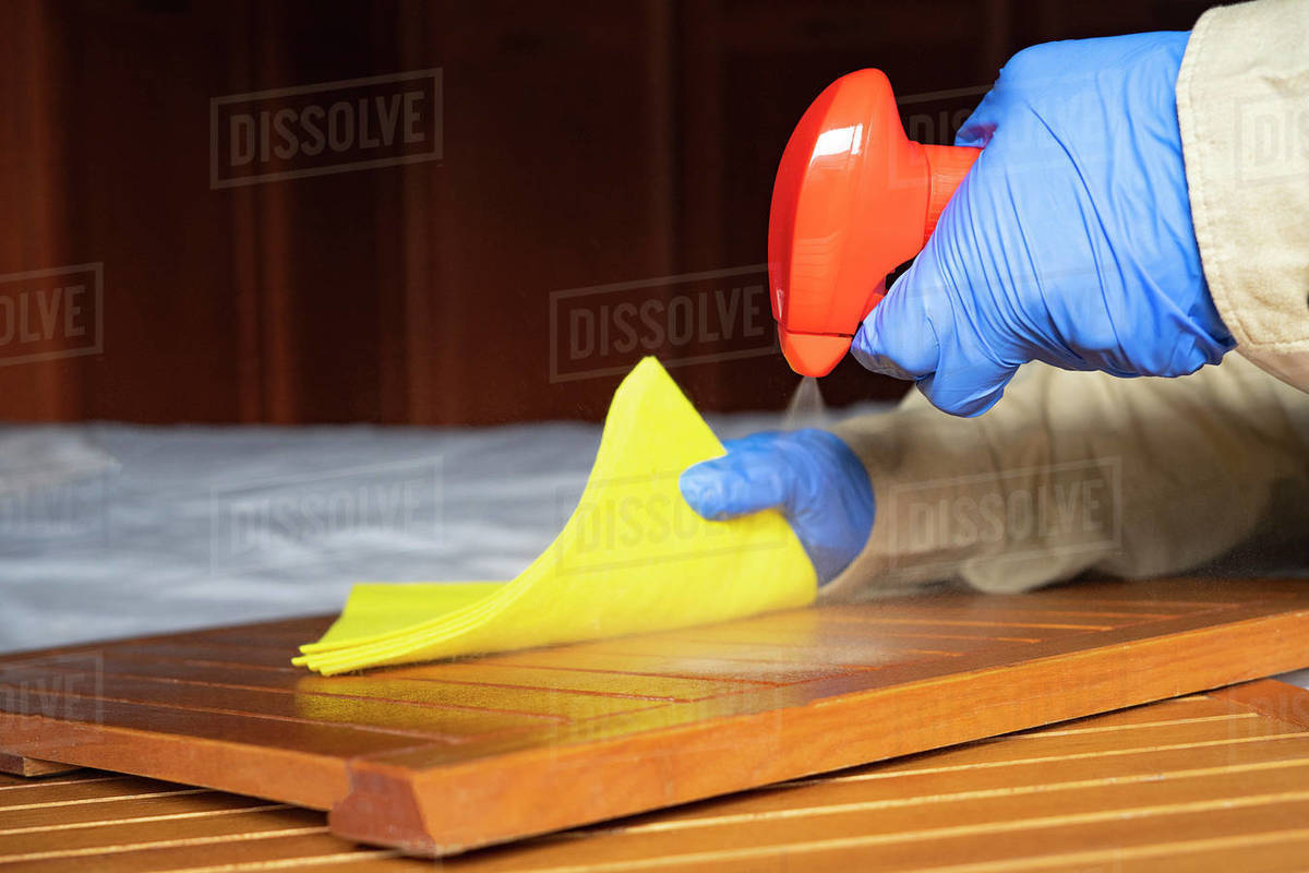 Man with gloves disinfecting a desk in the office. Royalty-free stock photo