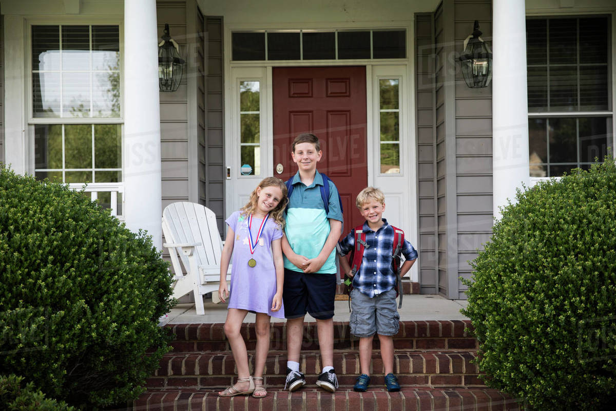 Three Smiling Happy Siblings With Backpacks Stand on Brick Front Steps Royalty-free stock photo