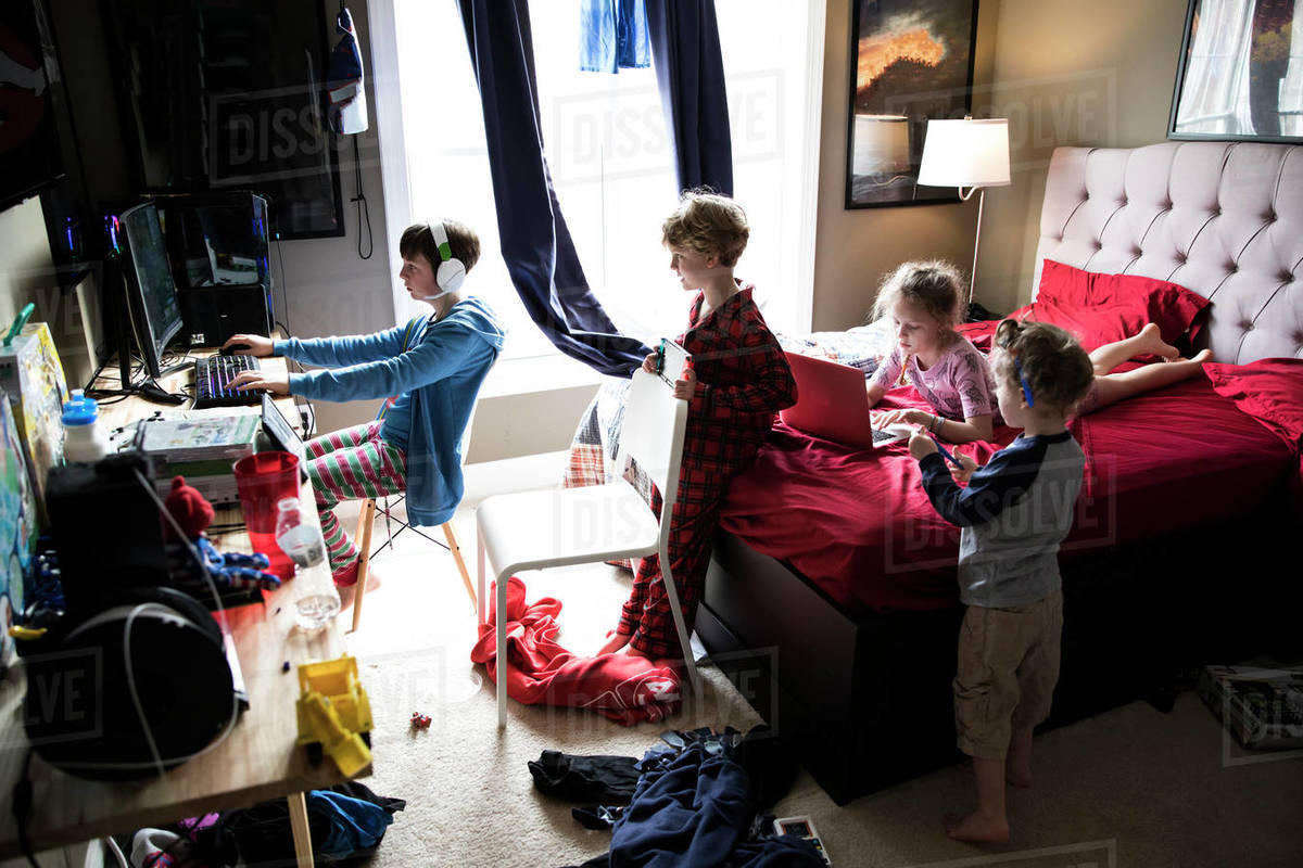 Four Siblings Hanging Out in Messy Teenage Brothers Bedroom Royalty-free stock photo