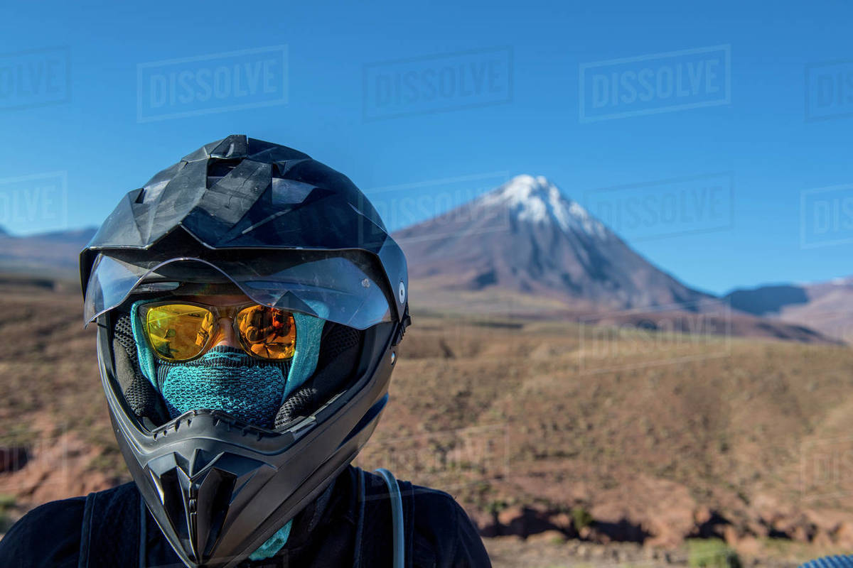 Woman with motorbike helmet, in front of the stratovolcano Licancabur Royalty-free stock photo