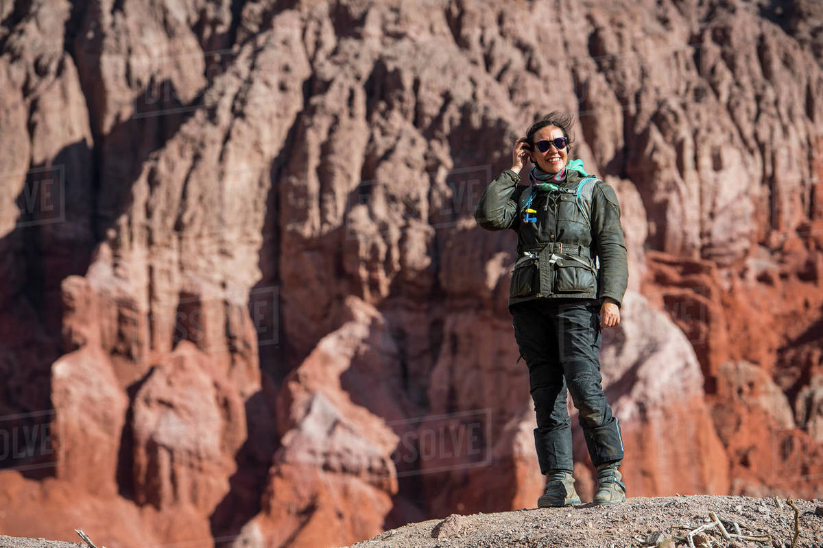 Woman in motorcycle gear, standing in front of red sandstone formation Royalty-free stock photo