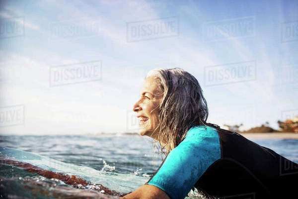 Side view of happy mature woman lying on surfboard in sea Royalty-free stock photo