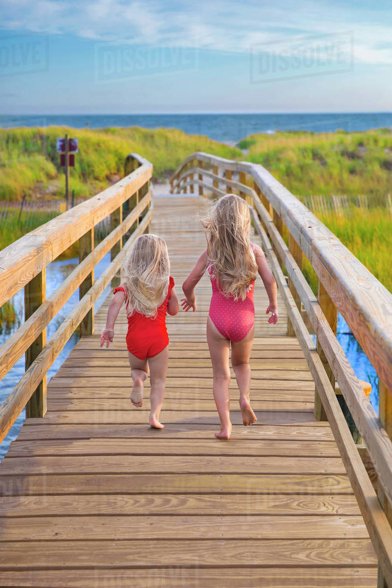 Little Girls From Behind Running On Bridge to Beach Royalty-free stock photo
