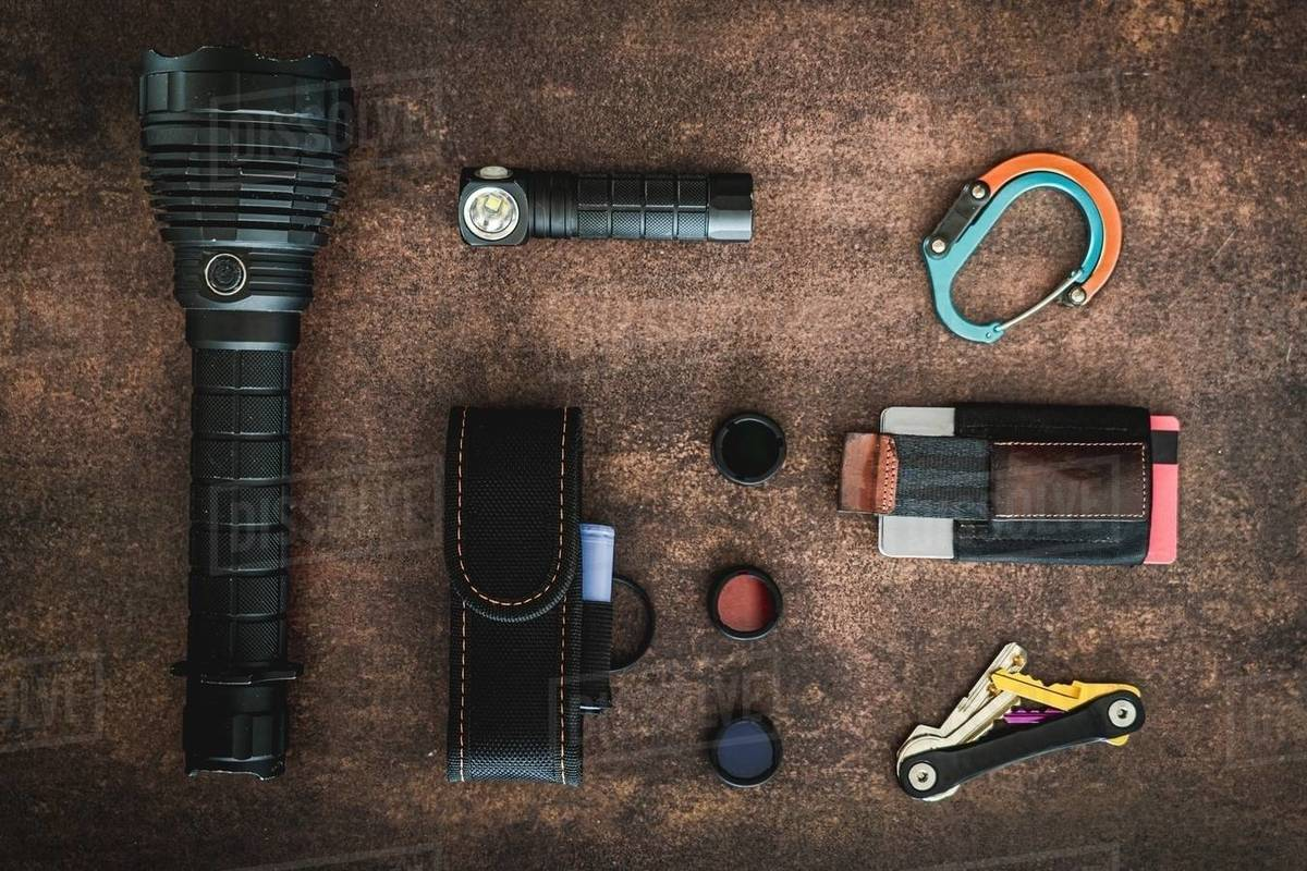 An amount of some EDC (Everyday carry) items on a wooden surface. There are some flashlights, a clip, a minimalist wallet, 3 flashlight filters, a flashlight cover and a key organizer keychai Royalty-free stock photo