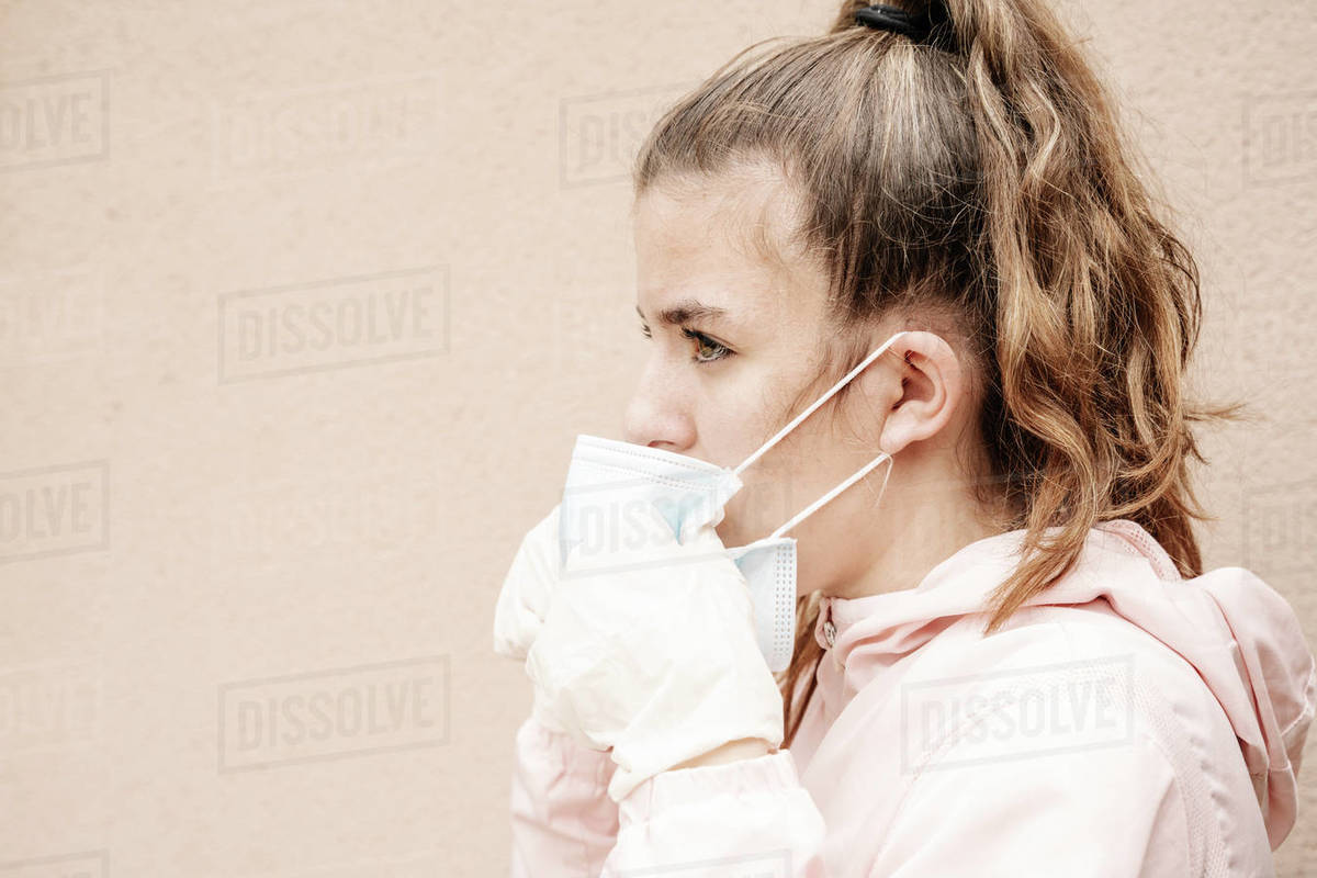 One blonde girl wearing latex gloves and face masks is showing the way she protects herself from coronavirus, bacterias, virus, fungus, etc. She removed mask to take clear breath. Horizontal Royalty-free stock photo