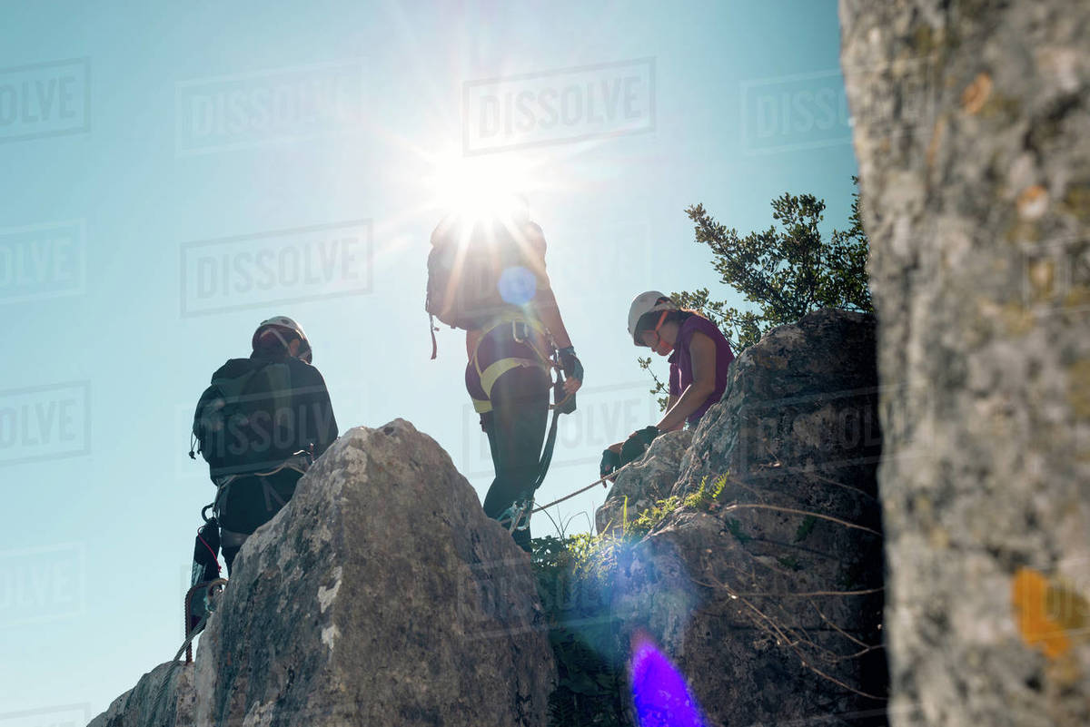 Concept: adventure. Three people with harness, backpack. Standing on top of the rock with backlit sun star. Royalty-free stock photo