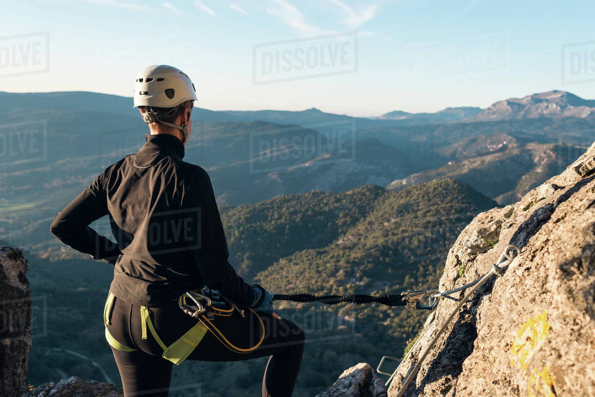 Concept: adventure. Climber woman with helmet and harness. From the back looking at the natural landscape of Andalusia. Secured to the natural wall with a carabiner. Via ferrata in the mounta Royalty-free stock photo