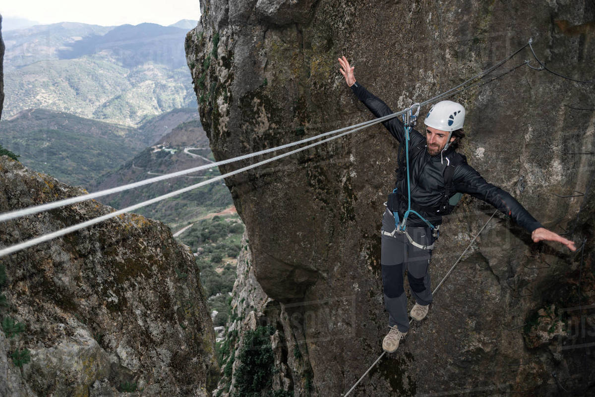 Concept: adventure. Climber man with helmet and harness. Balancing assured on a Tibetan cable bridge. Climbing to the top of the mountain. Via ferrata on rock. Royalty-free stock photo